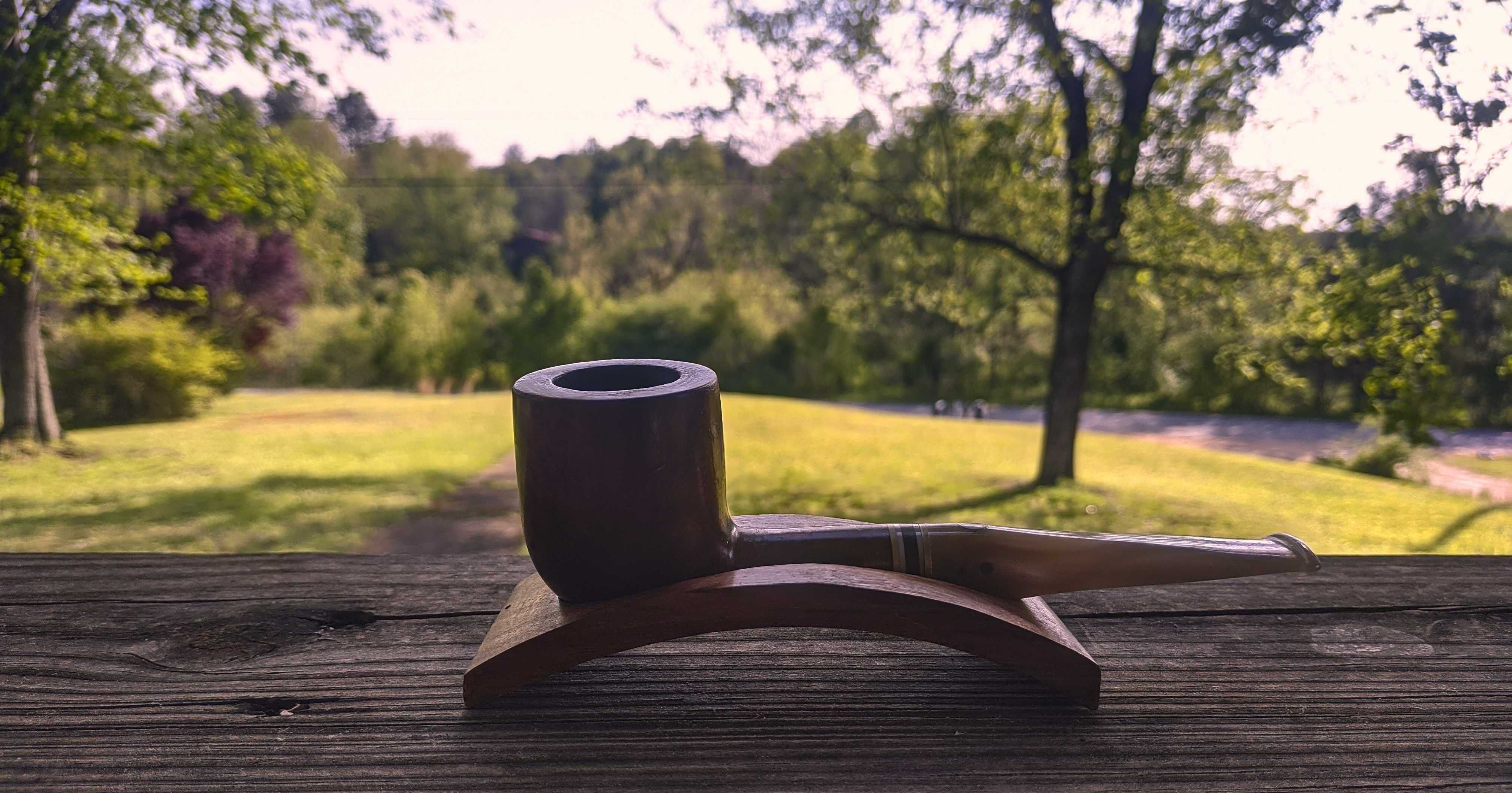 A picture of my pipe from Mauro Armellini. It's sitting on my porch rail with the yard in the background; the grass is a light green and the leaves of the woods further on are darker. The pipe is a rich brown with a cream-coloured opalescent stem. There is a mother-of-pearl inlay on top of the stem.